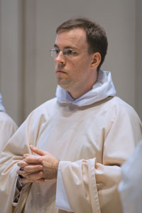 Father Pius at mass following his ordination, wearing a white chasuble, the liturgical garment of the priest.