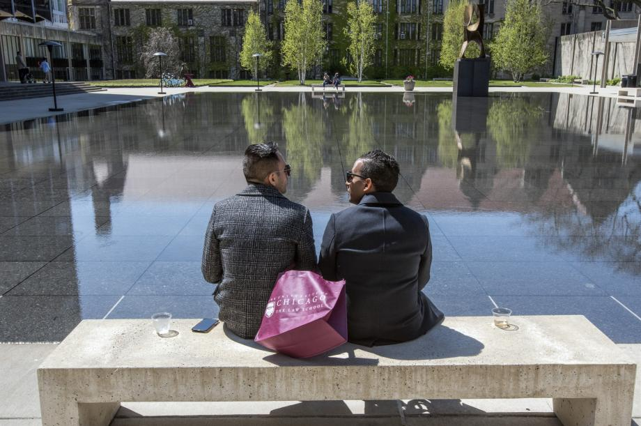 Two alums look out over the reflecting pool.