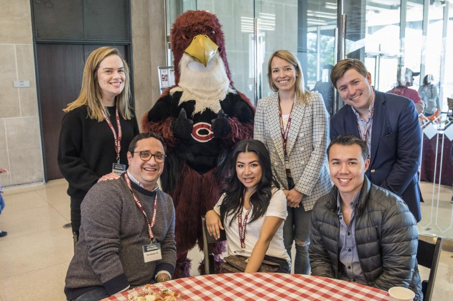 A group of alumni met mascot Phil the Phoenix in the Green Lounge.